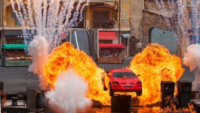 A car flies over a burning course in the Lights, Motors, Action! Extreme Stunt Show