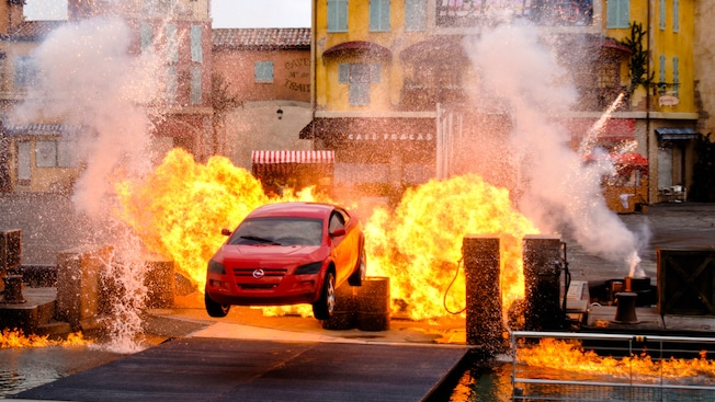 Red car flying through a flaming explosion at Lights, Motors, Action! Extreme Stunt Show
