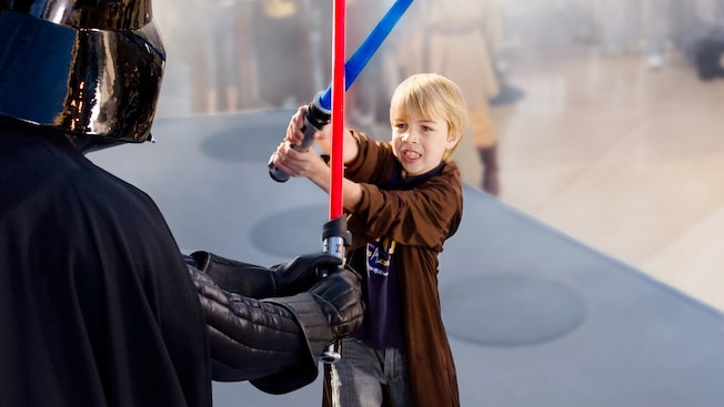 Little blonde boy wields a light saber at Darth Vader during Jedi training