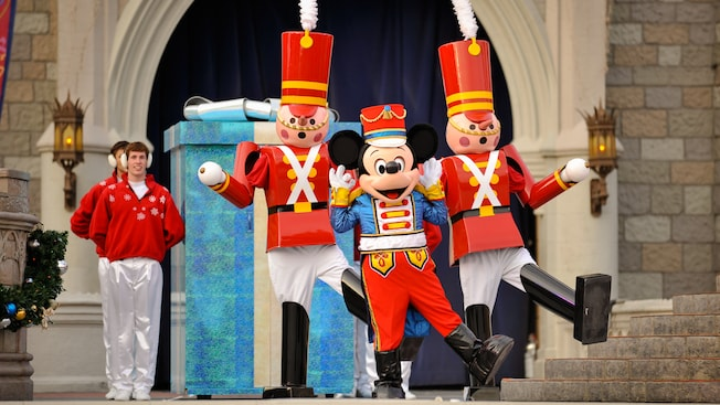 Mickey Mouse and 2 toy soldiers dancing on the steps of Cinderella's Castle at a Christmas Party
