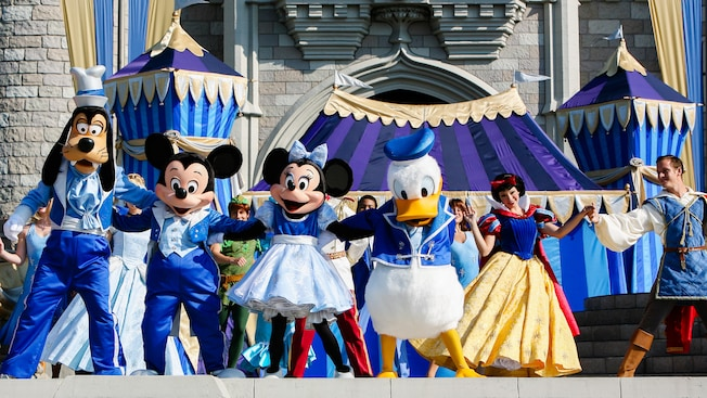 Goofy, Mickey, Minnie, Donald and Snow White stand with arms intertwined on stage during Dream Along With Mickey