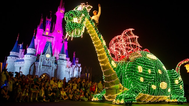 A train engine carrying Goofy and a drum with Minnie at the Main Street Electrical Parade