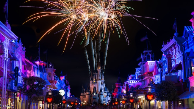 Fireworks from Cinderella Castle light the night sky on a street with Mickey Mouse-themed lanterns