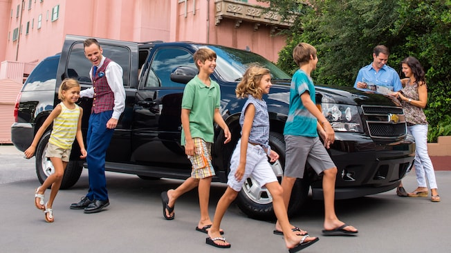 A VIP Tour Guide smiles as he delivers an excited family to a Walt Disney World Resort destination