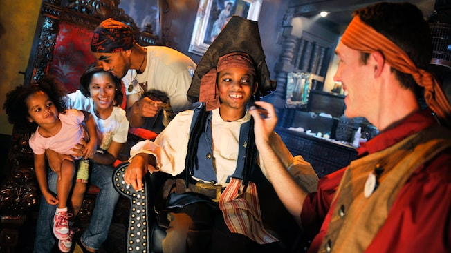 Mom and daughter watch as Dad and son get a pirate makeover at the Pirates League
