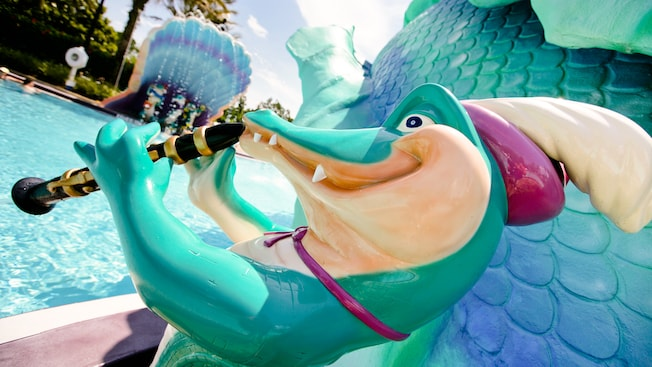 Sculpture of an alligator in a plumed cap playing a clarinet next to Scales, the sea serpent waterslide at Doubloon Lagoon Pool