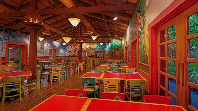 Dining area with colorful tables and murals at Pizzafari restaurant