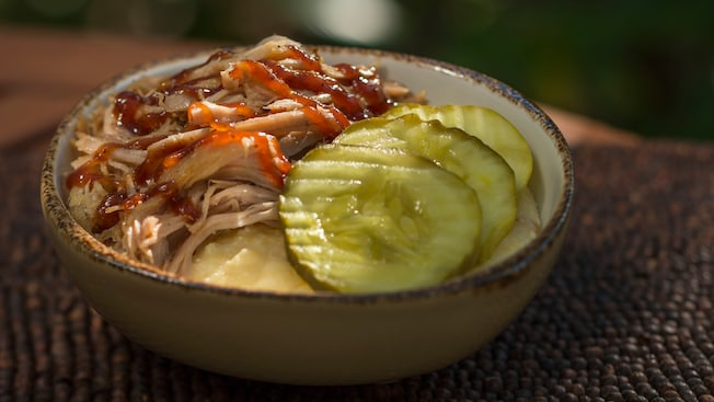 A bowl with pulled pork and pickles, with cheddar grits peeking out from the bottom