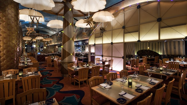 Long view of dimly lit dining room at Flying Fish Café, with mini parachutes overhead