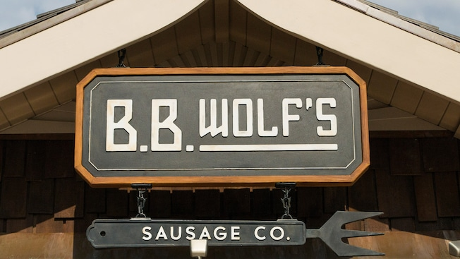 An industrial sign that reads B B Wolf's Sausage Co featuring a fork design at the bottom