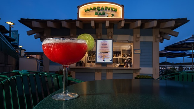 Close-up of a strawberry margarita on a patio table, with an outdoor 'Margarita Bar' in the background