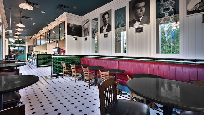 Seating area inside Cookes of Dublin, with black-and-white portraits and red banquettes