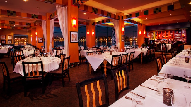 Panoramic view of The Dining Room at Wolfgang Puck Grand Café, lit up at night
