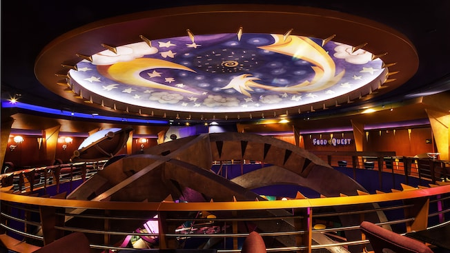 Top-floor view inside DisneyQuest of large, circular ceiling light-fixture with a celestial design