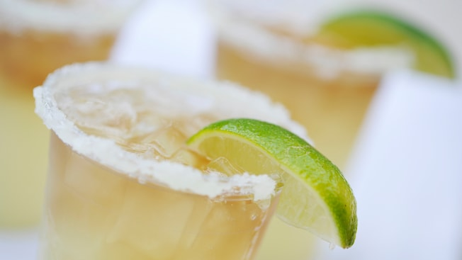A trio of refreshing margaritas served on the rocks, each garnished with a lime and salt on its rim