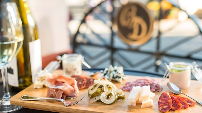 An ornately dressed cheese and charcuterie board displayed beside a glimmering glass of chardonnay