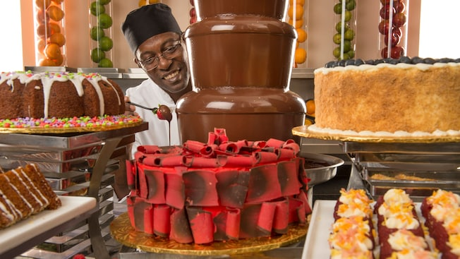 A pastry chef stands near a chocolate fountain amidst cakes, cupcakes and other pastries