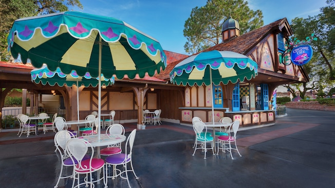 Colorful umbrella tables and chairs outside Cheshire Café in Fantasyland