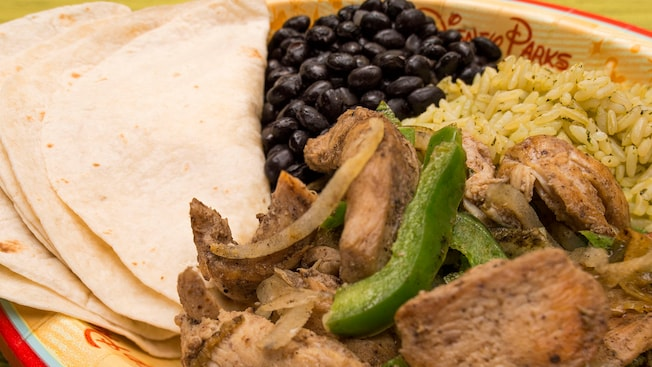 A plate of chicken, bell peppers, black beans, rice and tortillas