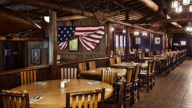 Old West-themed dining room with exposed timbers and washboards and copper pots as décor
