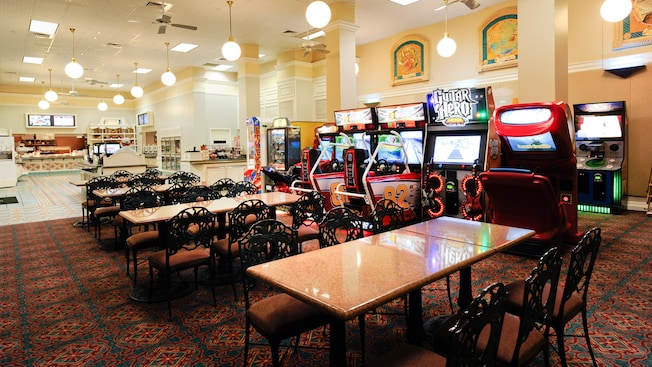 Large, brightly lit room with a carpeted area featuring video games and a row of tables with seating for 6