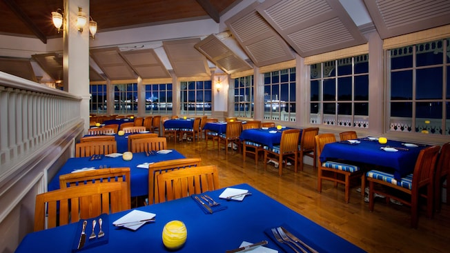 Restaurant with royal blue table clothes and white china in a window-filled white room