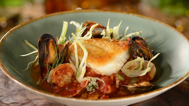 A bowl containing cioppino seafood stew includes a piece of grilled fish, mussels, clams and herbs in a tomato based broth
