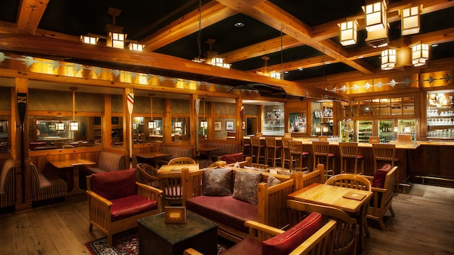 Bar and lounge area with floor-to-ceiling wood beams and oars decorating posts between booths