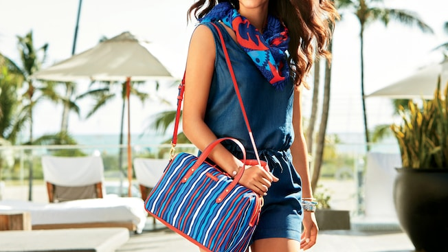 A woman strolls outdoors with a Vera Bradley Preppy Poly Marlo satchel on her shoulder and the Printed Poly scarf around her neck