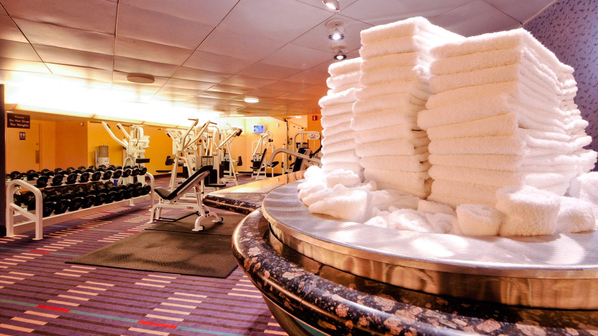 3 piles of folded white towels on a marble table in a workout room with free weights and other workout equipment in the background