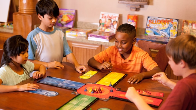 A group of children gather around a table to play a board game together