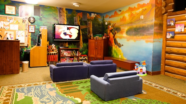 A kid's Western-themed play space in Disney's Wilderness Lodge featuring a flat-screen TV, sofas and toys