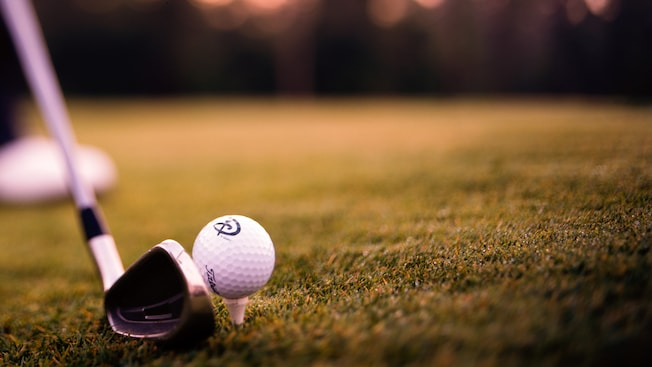 Close-up of a golf club about to hit a golf ball on a tee