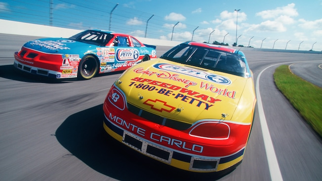 "2 stock cars covered with decals including ""Petty"" and ""Walt Disney World"" race on the speedway"