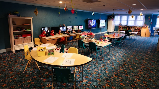 A nautical-themed activity center for children, featuring tables for arts and crafts, and 2 flat-screen TVs