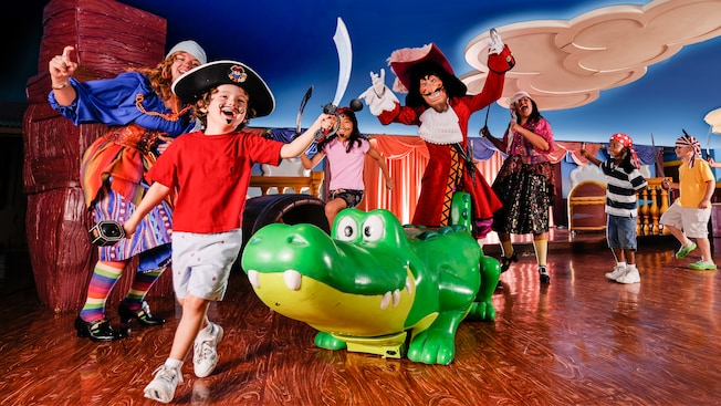 Kids and Cast Members, dressed as pirates, perform on a stage with Captain Hook and an alligator statue
