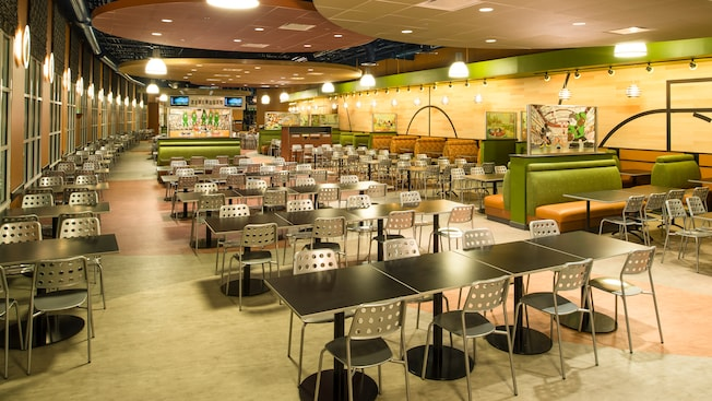 Un área de comidas con decoración moderna, mesas, sillas, cubículos, obras de arte e iluminación cenital