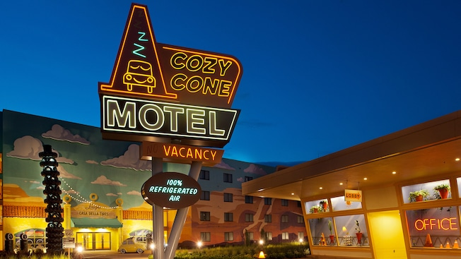 The neon Cozy Cone Motel sign outside the Cars Family Suites at dusk