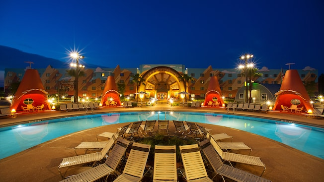 The Cozy Cone Pool illuminated at dusk, complete with lounge chairs and large traffic cone cabanas