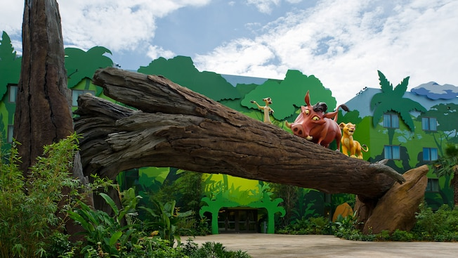A larger-than-life Timon, Pumbaa and Simba cross a log outside The Lion King Family Suites