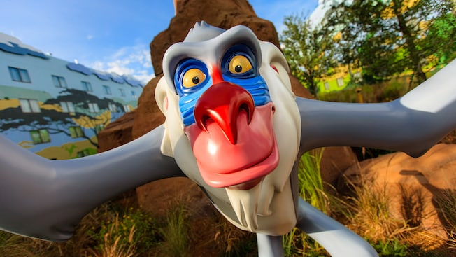 A life-sized figure of a smiling Rafiki from Disney's The Lion King in the courtyard of The Lion King Family Suites