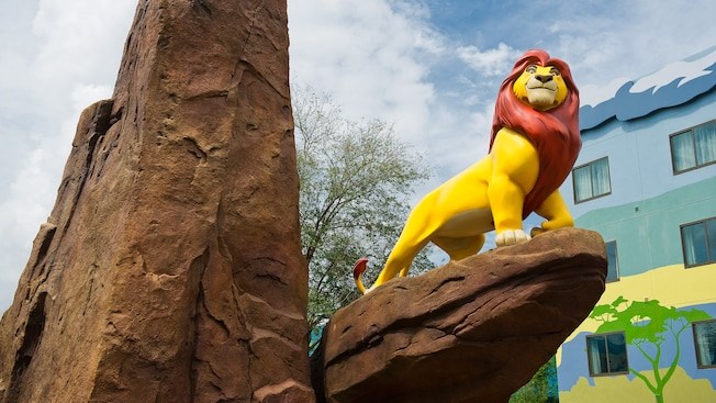 A life-sized King Mufasa majestically stands atop Pride Rock outside The Lion King Family Suites