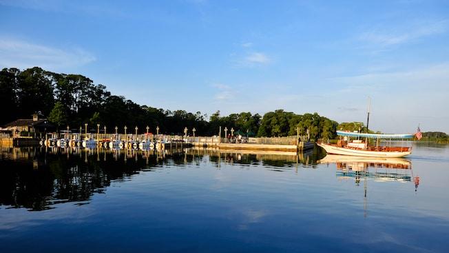 Un ferry en el agua plácida se detiene en un muelle bajo un cielo azul claro