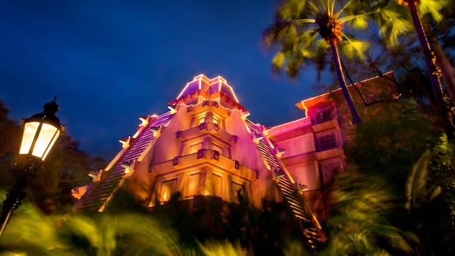 Aztec temple-like building in the Mexico Pavilion bathed in magenta light at night