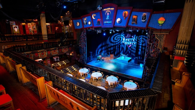 A balcony containing church pew seating overlooks the ground floor and stage of House of Blues Music Hall which is set with a drum kit, percussion instruments and a grand piano