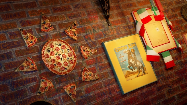 Italian flags, framed book covers and pizza-shaped art on brick wall