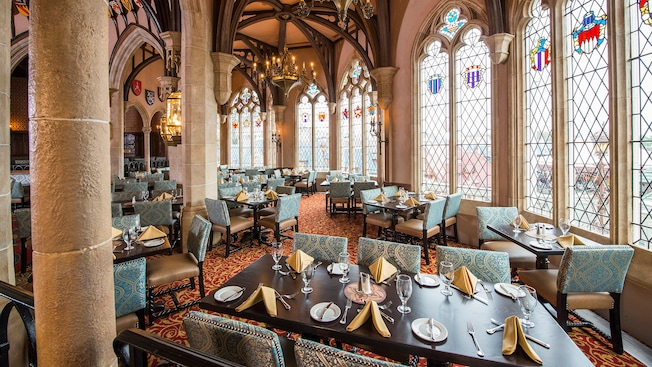 Elegant table setting at Cinderella's Royal Table, with soaring stone archways and stained-glass windows