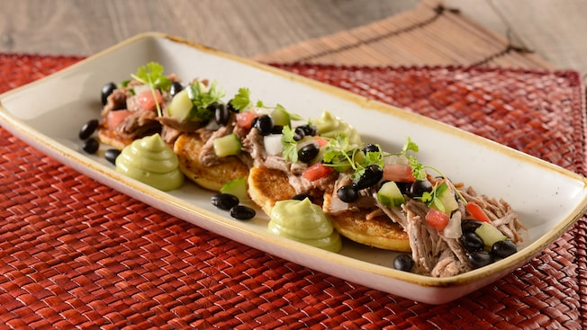 An appetizer plate containing mini corn pancakes, braised pork, black bean salad and avocado cream