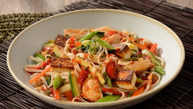 Noodle salad with zucchini, peas, carrots, bell peppers, chicken and tofu