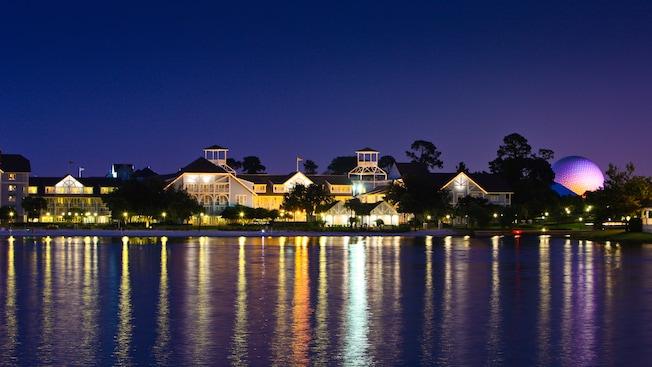 Vista desde el otro lado de Crescent Lake en Disney's Beach Club Resort, iluminada por la noche